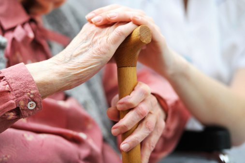 Elderly woman in a Nursing Home and her Caregiver hold hands