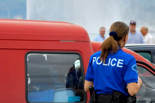 A police officer approaches the accident scene.