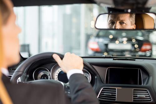 Man looking at rear-view mirror